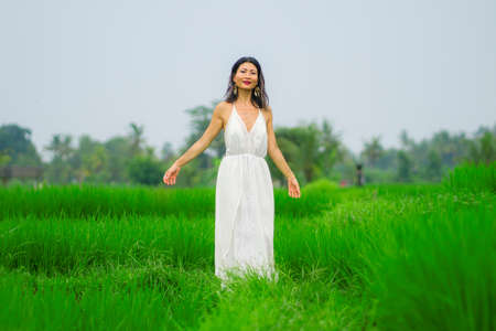 lifestyle portrait of young attractive and happy Asian woman outdoors at green rice field landscape wearing elegant long dress enjoying nature carefree and delighted