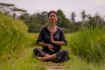 artistic portrait of young attractive and happy Asian woman outdoors at green rice field landscape dancing and doing yoga relaxation exercise and meditation
