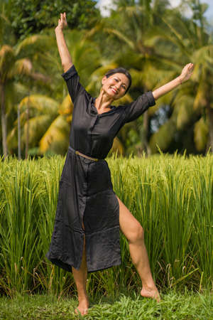 artistic portrait of young attractive and happy Asian woman outdoors at green rice field landscape dancing and doing spiritual meditation on beautiful nature background Foto de archivo