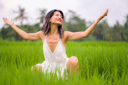 artistic portrait of young attractive and happy Asian woman outdoors at green rice field landscape wearing elegant long dress enjoying playful on beautiful nature Foto de archivo