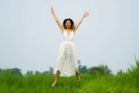 artistic portrait of young attractive and happy Asian woman outdoors at green rice field landscape wearing elegant long dress relaxed and carefree enjoying nature