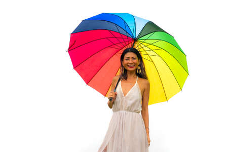 attractive and happy Asian woman holding rainbow colorful umbrella or parasol smiling playful isolated on white background in beauty and freedom concept
