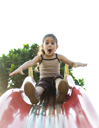 A naughty little girl is sliding down a slide on a playground