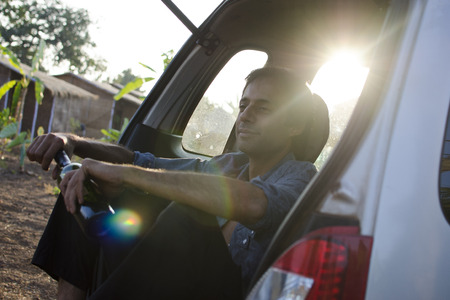 wine road: A young man is enjoying the freedom of a road trip and is having some wine straight from the bottle