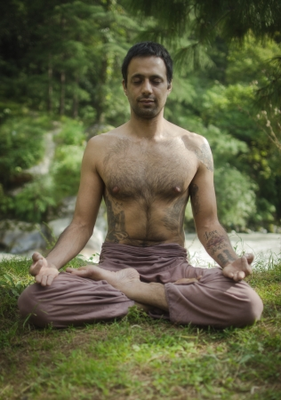 A young man is practicing Yoga, Pranayama and Meditation in a peaceful Himalayan forest next to a river  photo