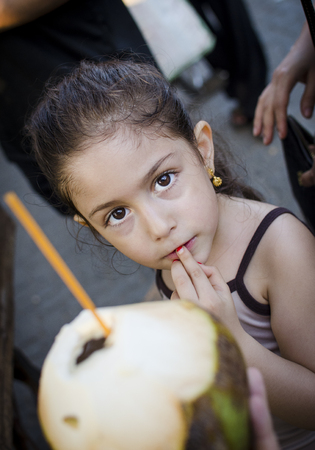 diarrhoea: Little girl having a Coconut drink in an exotic country Stock Photo