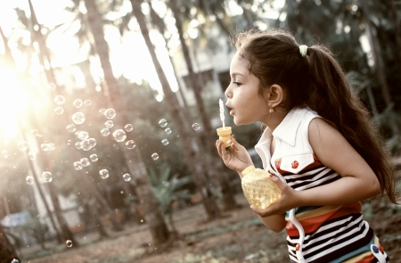 A little girl is having fun making soap bubbles in a park  photo
