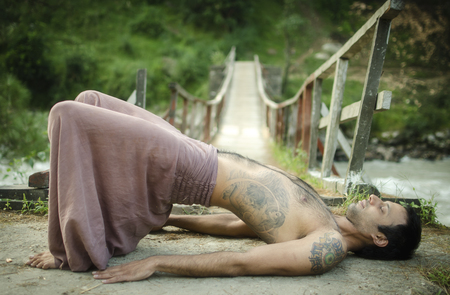 sadhu: Man practicing the half-bridge position of Yoga in a Himalayan forest
