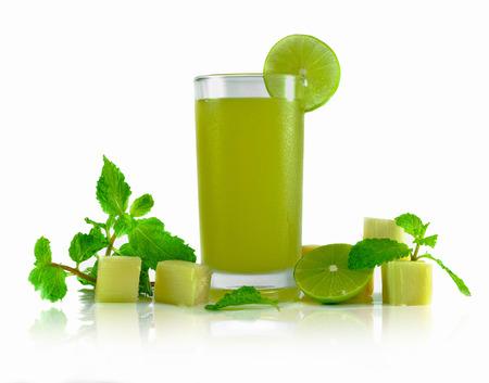 zumo verde: toma jugo de la ca�a de az�car con la decoraci�n de la cal en el fondo blanco