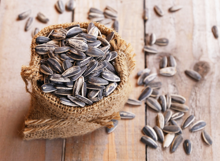 sunflower seeds: pile of sunflower seeds in the small sack on the wooden background Stock Photo