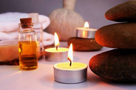 spa conception with stone balance and candle flame, oil massage