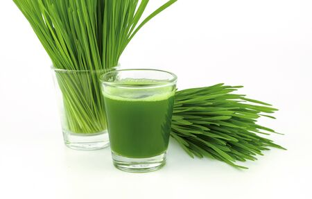 close up wheat grass juice on white background