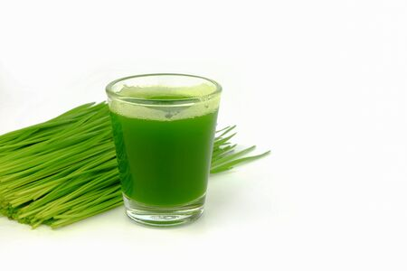 close up wheat grass shot in small glass on white backgound Stock Photo