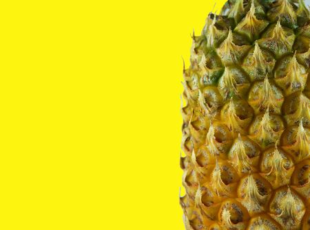 haft of pineapple on the yellow background