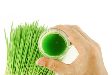 man hold shot of wheat grass juice to drinking on white background