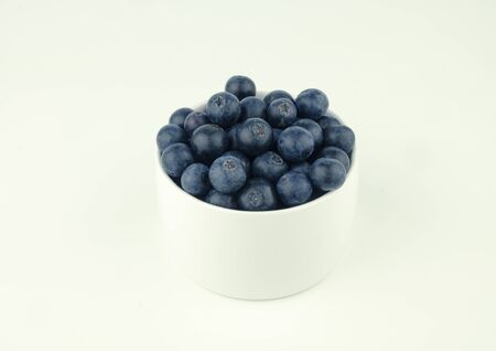 ripe blueberry on white bowl on white background Stock Photo