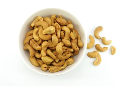 top view of roasted cashews nut in white bowl on white background