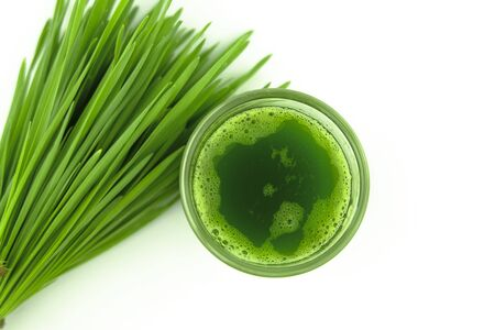 top view of wheat grass juice in glass on white background