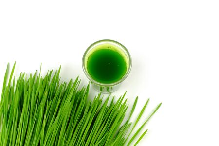 shot of detox juice beside pile of wheat grass on white background Stock Photo - 132135865