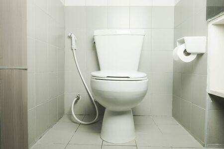white ceramic toilet bowl in bathroom with toilet paper