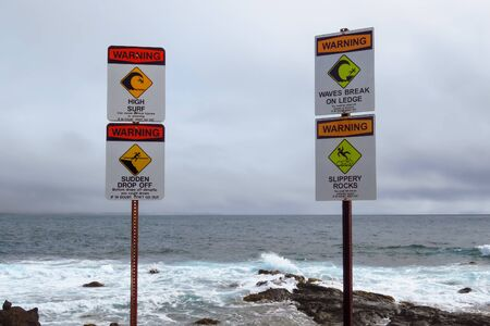 Sea warning signs 'High Surf' 'Sudden Drop Off' 'Waves Break On Ledge' 'Slippery Rocks', Ahukini, Kauai, Hawaii, USA