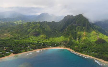 Aerial view over blue bay, golden beach, green mountains and misty clouds in Na Pali Coast State Wilderness Park, landscape photo taken from a helicopter, Kauai, Hawaii, USA 写真素材