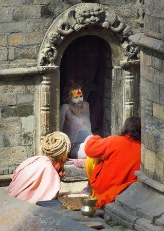 Kathmandu, Nepal - 11142017: Sadhus, ascetic holy men, sit at Pashupatinath Hindu Temple, Kathmandu, Nepal