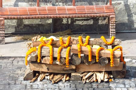 Funeral pyre of wood adorned with marigold flowers for cremation of a dead loved one near the Bagmati River at the Hindu Pashupatinath Temple, Kathmandu, Nepal Stock Photo