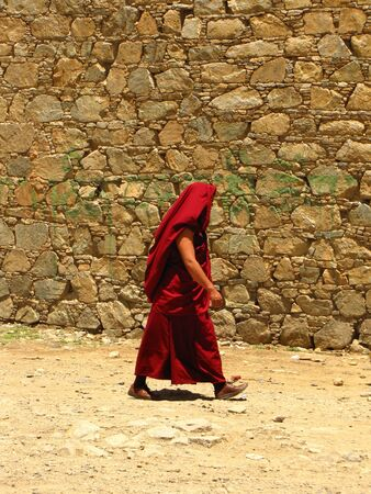 Monk in red clothes walking next to a wall, covering his head as a protection for the sun, at Samye monastery, Tibet, China Stockfoto