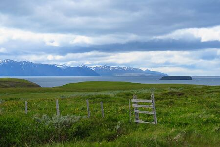 Fence in field, green grass, fjord lake and mountains in the background, Tjornes peninsula, Iceland, Europe Stock fotó