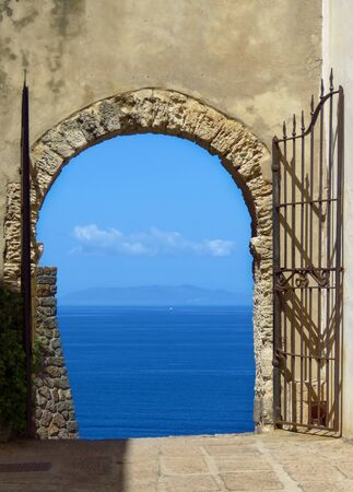 Open gate showing a marvelous view on the mediterranean sea, blue sky and blue ocean, Cala Spinosa, Sardinia, Italy, Europe