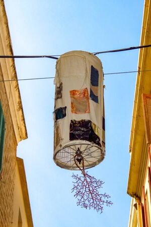 Nicely decorated street light, creative lamp against a blue sky in the city of Alghero, Sardinia, Italy