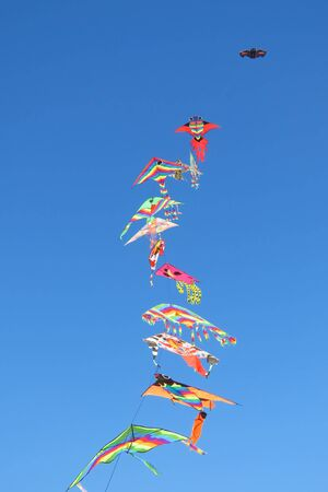 Colorful kites in the blue sky, beach fun for young and old, Spiaggia Su Giudeu, Sardinia, Italy, Europe Banco de Imagens