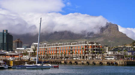 V&A Waterfront marina and Table Mountain partly covered with clouds, Cape Town, South Africa