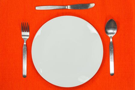 White empty plate with fork, spoon and knife on a orange tablecloth  photo
