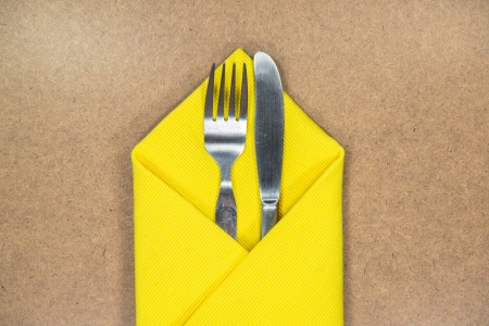 fork and knife in yellow napkin