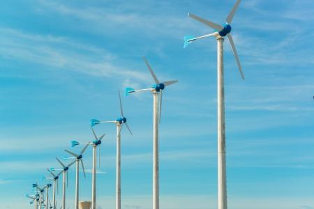 white wind turbine generating electricity on blue sky photo