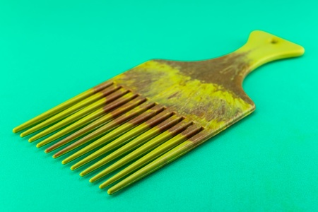 long handled: Comb isolated on green background