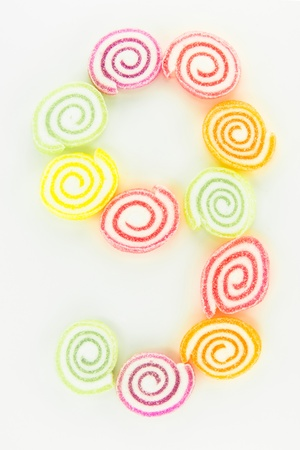 number 9 written with slices of dried sweet candies photo