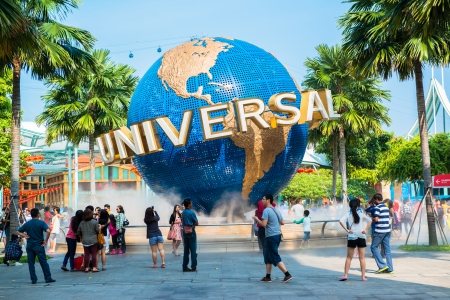 SINGAPORE - JANUARY 26  Tourists and theme park visitors taking pictures of the large rotating globe fountain in front of Universal Studios on January 26, 2014 in Sentosa island, Singapore