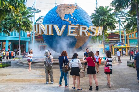 SINGAPORE - JANUARY 12 Tourists and theme park visitors taking pictures of the large rotating globe fountain in front of Universal Studios on January 12, 2015 in Sentosa island, Singapore