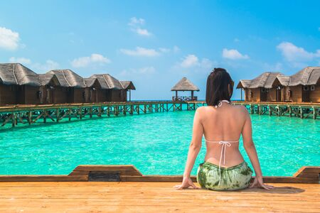 Woman is relaxing on the water bungalow of the tropical beach, Maldives Stock Photo