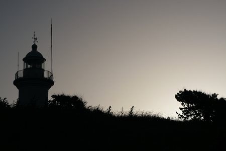 a lighthouse silhuette on the evening photo