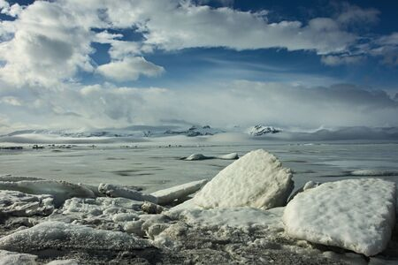 ice floe: Ice floes in front of frozen glacier lake and mountain panorama in Iceland