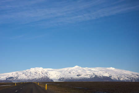 on the lonely road: Icelandic landscape behind lonely road in front of blue sky