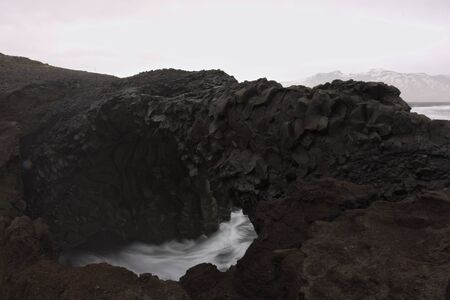 caved: Volcanic stone bridge caved out by the wild sea Stock Photo