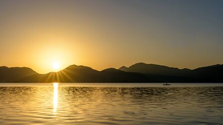 Sunrise over mountains and lake with canoeist Stock Photo