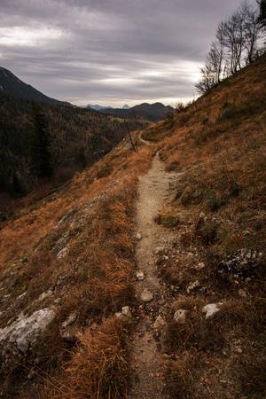 Little path leads in wide mountain landscape under cloudy sky