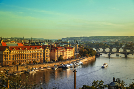 View of Charles bridge and the old town of Prague in Czech Republic, at the banks of Vltava River under the sunset