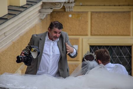 Vienna, Austria, September , 15, 2019 -  A engaged wedding photographer directs pictures of the bride and groom in Schonbrunn Palace. The photographer tries to put them in the mood.
